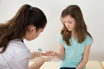 Healthcare professional measures a girl's blood sugar level
