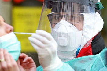 Healthcare worker wearing PPE performs a nasal swab